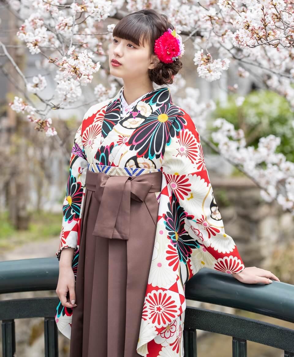 卒業式で袴レンタルしたい赤地の着物と茶色袴のコーデ