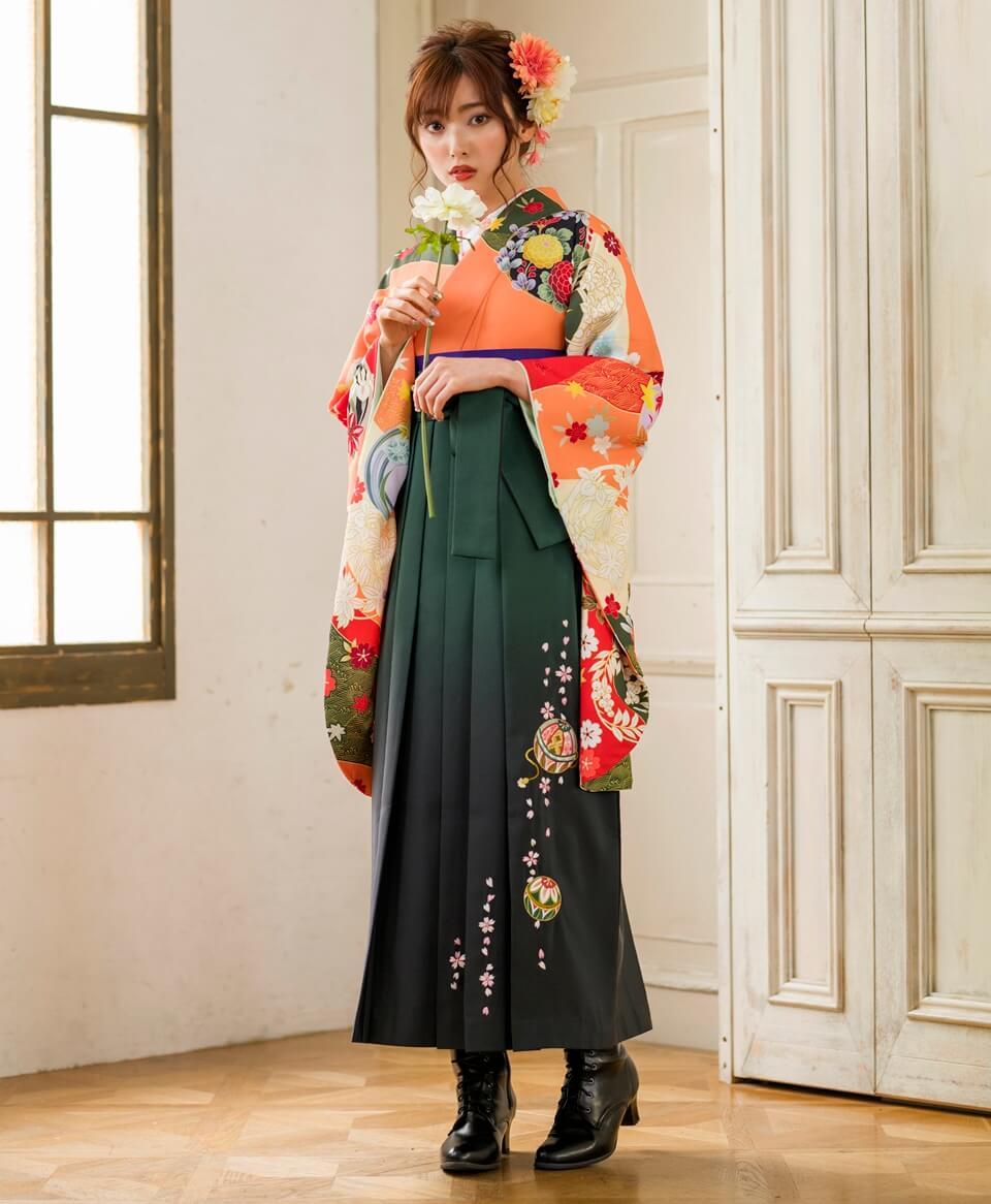 オレンジ色の着物に刺繍入りの深緑袴を合わせた小学生の袴