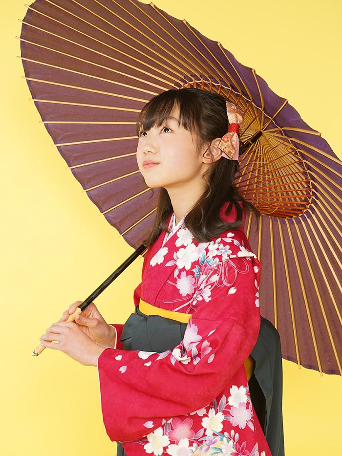 和傘を持って撮影している袴姿の小学生