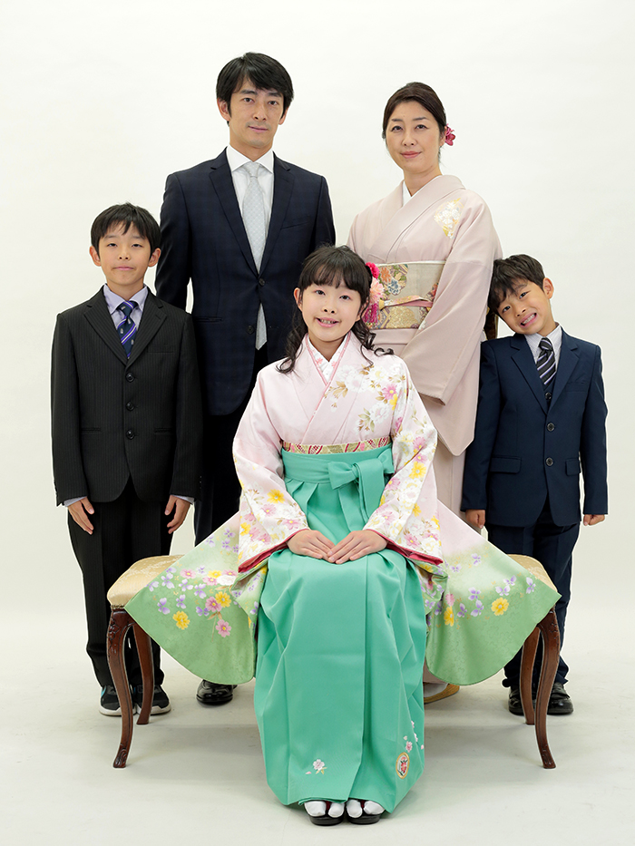 ご家族と一緒に写真を撮る袴姿の小学生